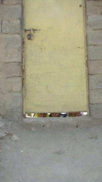 Chłopcy patrzą z podwórka na życie uliczne. Fot. Qamar Hashim